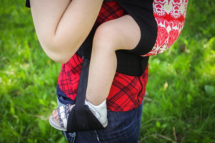 Детские ножки, вставленные в стремена эрго-рюкзака Боба (Boba Baby Carrier 3G)